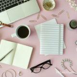 ピンクのテーブルの上のパソコンとノート